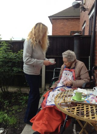 Elderly lady being given a cup of tea in the garden