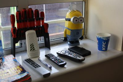 Window sill of personal possessions, including air freshener, remote controls, TV guide, cup, screwdrivers, phone and Minion figurine