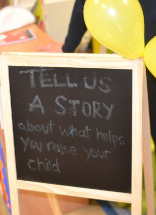 Community engagement sign 'tell us a story about what helps you raise your child'